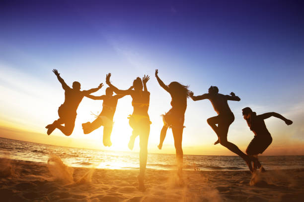 Happy friends jumps beach sunset. Friendship or team concept - foto stock