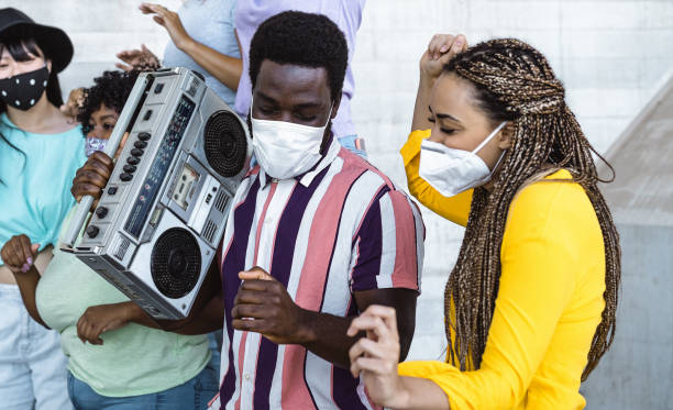 happy friends listening music with vintage boombox and dancing while wearing face mask outdoor - multiracial young people having fun during corona virus outbreak - youth millennial friendship concept - afro latino mask imagens e fotografias de stock