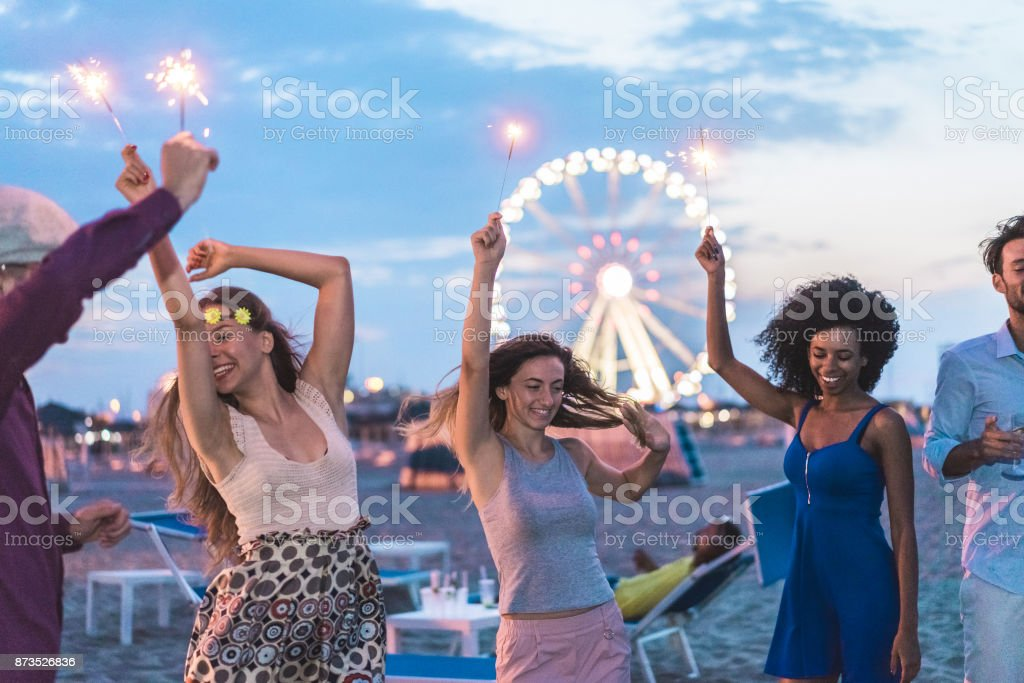 Happy friends making beach party after sunset with fireworks and drinking champagne - Young people having fun dancing outdoor  - Soft focus on center girl face - Youth and festival concept stock photo