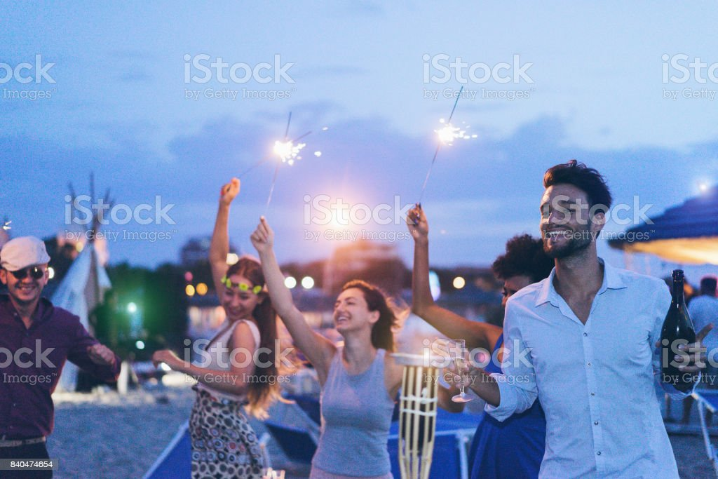 Happy friends making evening beach party outdoor with fireworks and drinking champagne - Young people having fun at chiringuito bar with dj set - Focus on right man face - Youth and summer concept stock photo