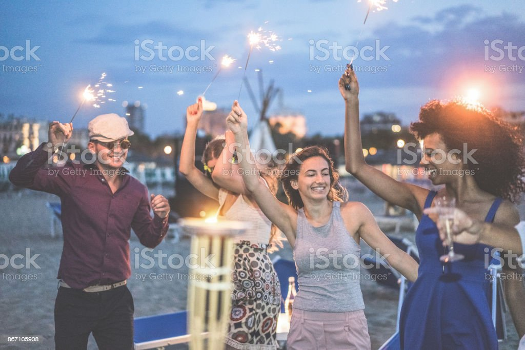 Happy friends making evening beach party outdoor with fireworks - Young people having fun dancing and drinking champagne - Soft focus on center woman hand - Vacation and nightlife concept stock photo
