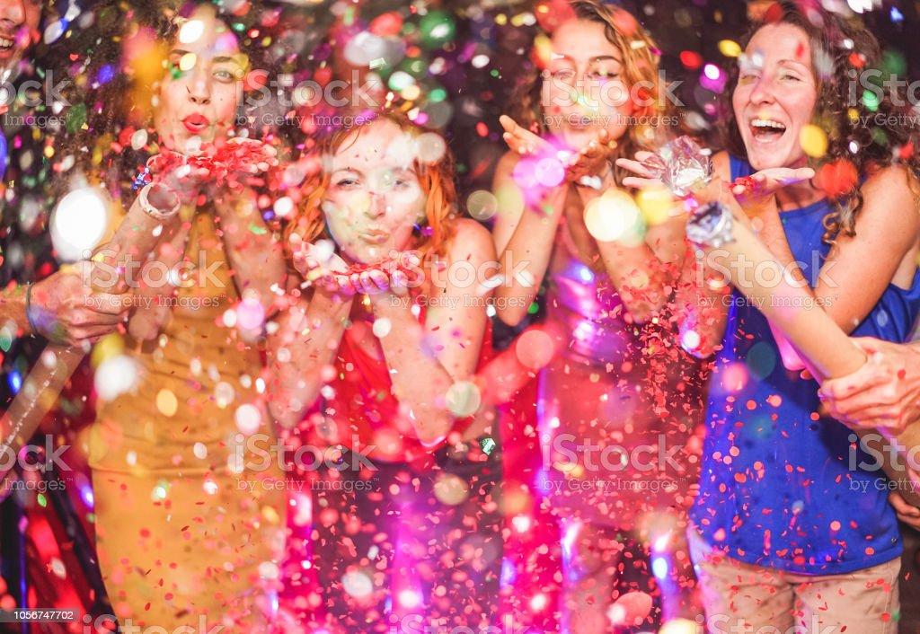 Amigos felices haciendo fiesta lanzando confeti - jóvenes celebrando en la noche del fin de semana - entretenimiento, diversión, fin de año, vida nocturna y fiesta concepto - centrarse en manos de la niña de pelo rojo foto de stock libre de derechos