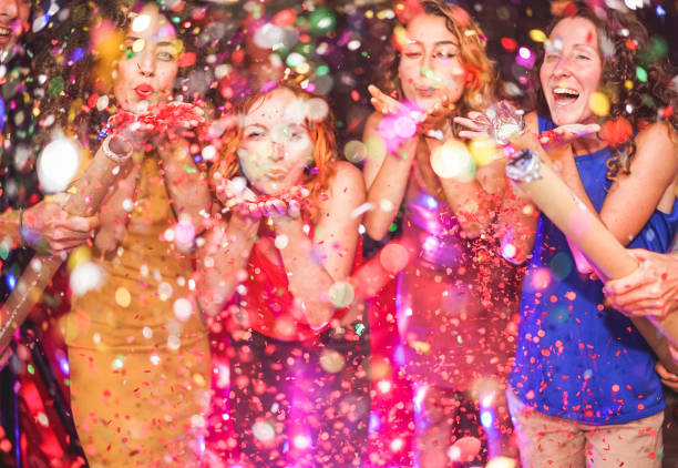 happy friends making party throwing confetti - young people celebrating on weekend night - entertainment, fun, new year's eve, nightlife and fest concept - focus on red hair girl hands - girls party zdjęcia i obrazy z banku zdjęć