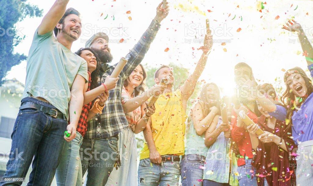 Glücklich Freunden Party machen, werfen Konfetti und mit bunten Rauchbomben auf Party im freien - junge Leute, die Spaß zusammen - weiche Links Mädchen und Fokus bärtige Gesichter - warme Kontrastfilter – Foto