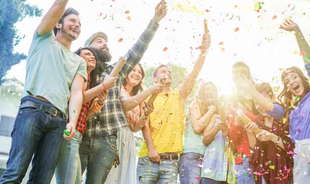 glada vänner göra parten, fokus kasta konfetti och använda färgglada rök bomber på fest utomhus - unga människor att ha roligt tillsammans - mjuk på vänster flicka och skäggig man ansikten - varma kontrast filter - happy indie pop bildbanksfoton och bilder