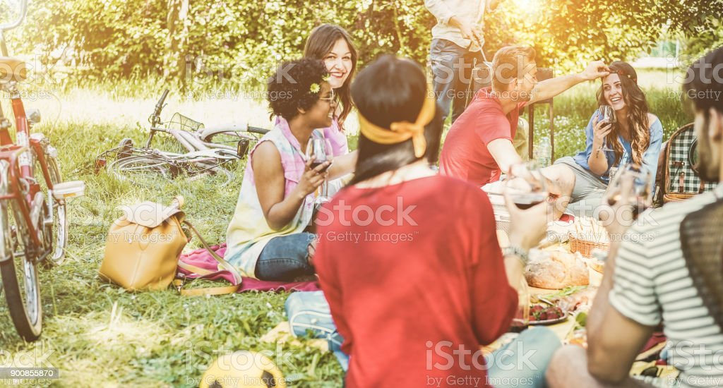 Happy friends making picnic barbecue meal outdoor - Young people having fun while eating and relaxing in nature - Focus on right girl face - Youth lifestyle, holidays and friendship concept stock photo