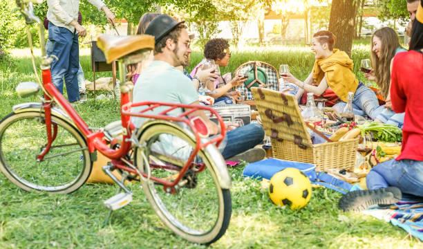 glückliche freunde machen picknick am stadtpark outdoor - trendigen jugendlichen wein trinken und essen gemeinsam im freien - fokus auf oben in der mitte mädchen und mann kochen bbq - jugend, essen und freundschaft konzept - mensch isst gras stock-fotos und bilder