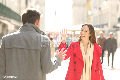 istock Happy friends meeting and greeting in the street 1044153942