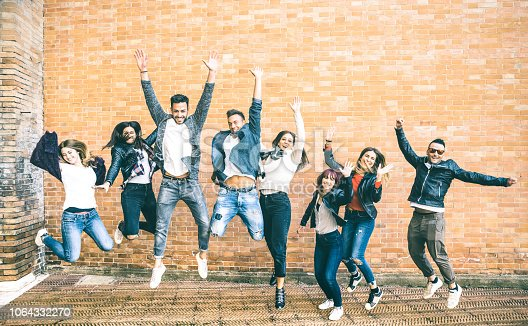 istock Happy friends millennials jumping and cheering against brick wall in the city - Friendship lifestyle and team concept with young people millenial having fun together - Teal and orange vintage filter 1064332270