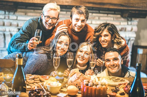 1064325668 istock photo Happy friends on group photo selfie celebrating Christmas time with champagne and sweets food at dinner reunion party - Winter holiday concept with people having fun eating together - Warm filter 1175537046