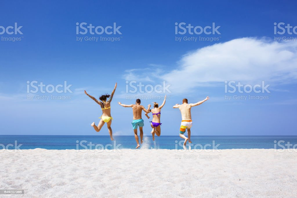 Happy friends on lonely beach stock photo