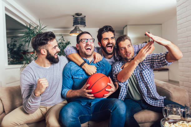 Happy friends or basketball fans watching basketball game on tv and celebrating victory at home.Friendship, sports and entertainment concept. Happy friends or basketball fans watching basketball game on tv and celebrating victory at home.Friendship, sports and entertainment concept. basketball sport stock pictures, royalty-free photos & images