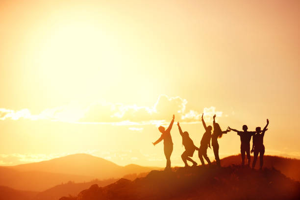 Happy friends or big family's silhouettes at sunset mountains