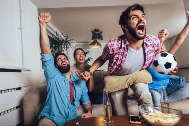 glückliche freunde oder fußballfans, die fußball im fernsehen beobachten und den sieg zu hause feiern. freundschafts-, sport-und unterhaltungskonzept. - fussball fan stock-fotos und bilder