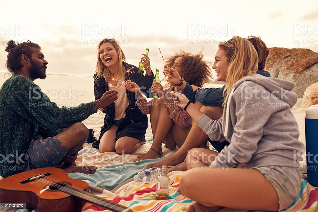 Happy friends partying on the beach stock photo