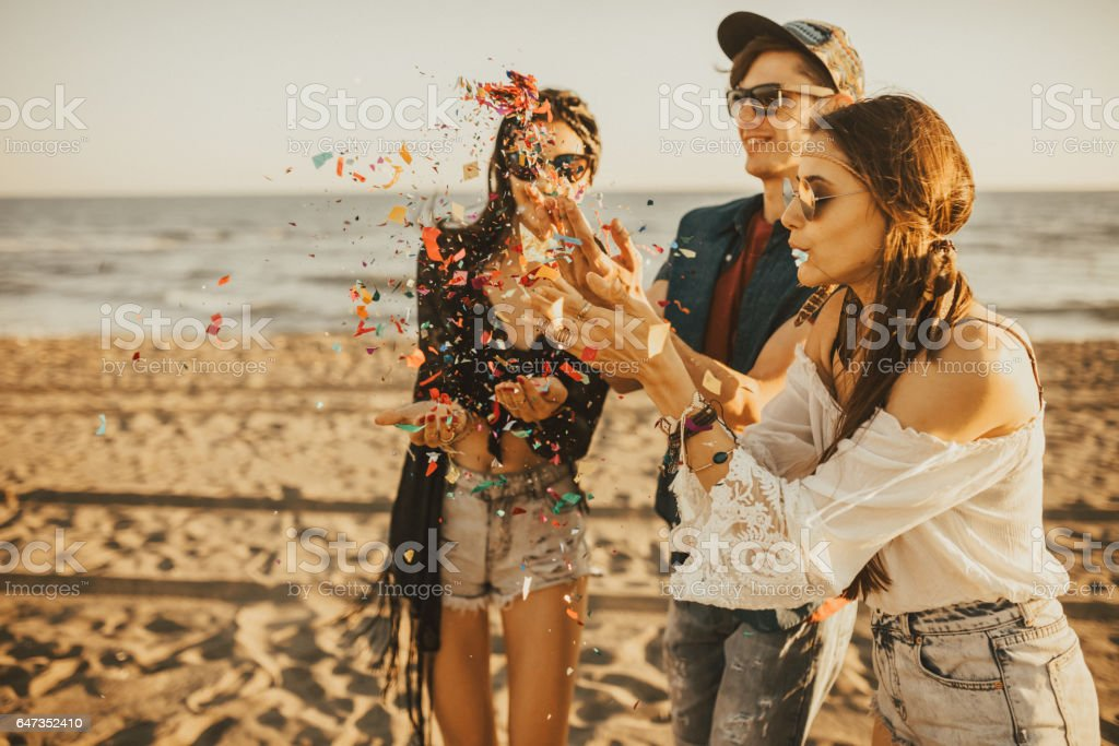 Happy friends partying on the beach with drinks and confetti. Happy young people having fun at beach party, celebrating with confetti. stock photo