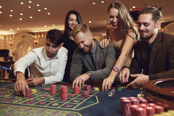 Happy friends play roulette in a casino. stock photo