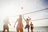 Happy friends playing beach volleyball on the beach