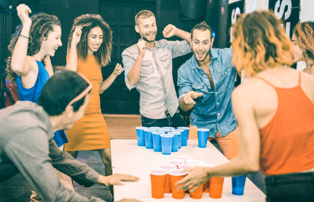 happy friends playing beer pong in youth hostel - travel and joy concept with backpackers having unplugged fun at guesthouse - young people on playful genuine attitude - teal and orange filter - beirut foto e immagini stock