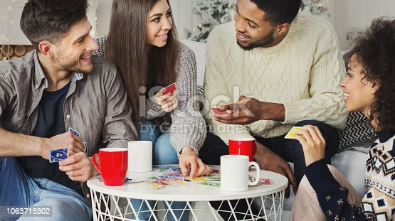 istock Happy friends playing game of cards UNO 1063715302