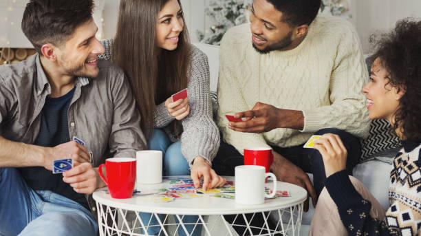 Happy friends playing game of cards UNO Multiracial friends having fun and playing game of cards UNO against christmas tree leisure games stock pictures, royalty-free photos & images