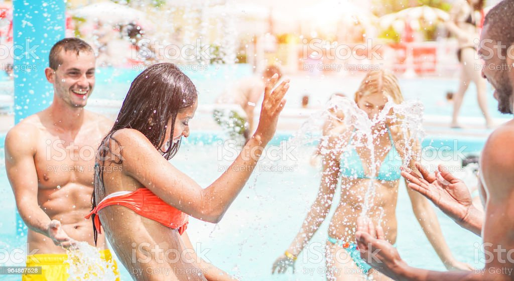 Happy friends playing in swimming pool party - Young diverse culture people having fun on summer vacation - Focus on latin woman face - Youth lifestyle, travel, holidays and friendship concept royalty-free stock photo