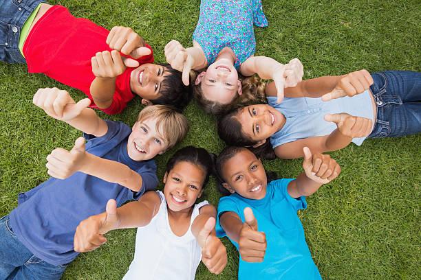 glückliche freunde spielen im park - kind vor der pubertät stock-fotos und bilder