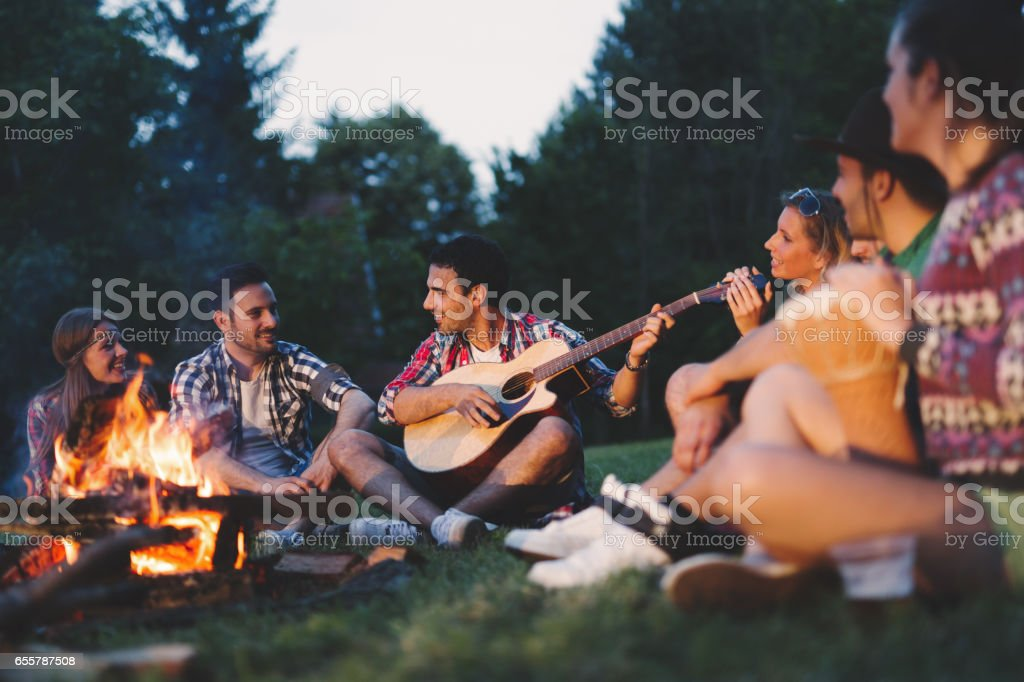 Happy friends playing music and enjoying bonfire in nature stock photo