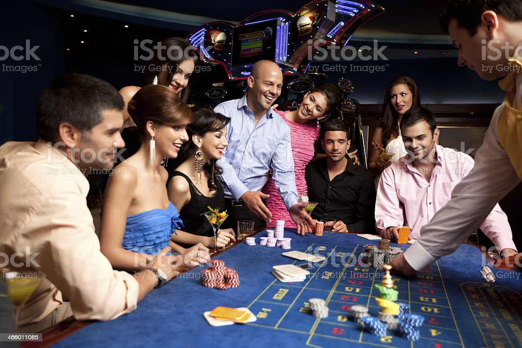 happy friends playing roulette in a casino stock photo