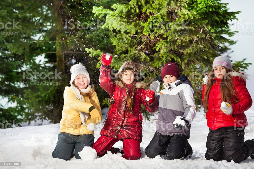 Happy friends playing snowballs at winter forest stock photo