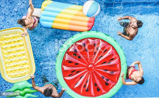 istock Happy friends playing with ball inside swimming pool - Young people having fun on summer holidays vacation - Travel,holidays,youth,friendship and tropical concept - Seasonal color tones filter 807560406