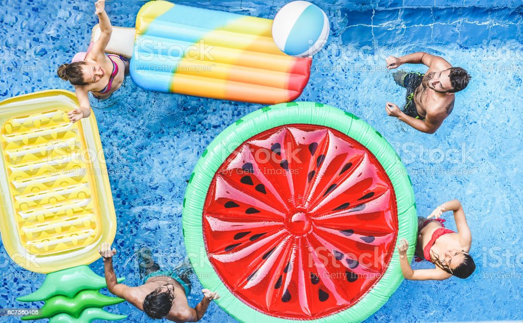 Happy friends playing with ball inside swimming pool - Young people having fun on summer holidays vacation - Travel,holidays,youth,friendship and tropical concept - Seasonal color tones filter - foto stock