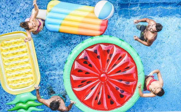 Happy friends playing with ball inside swimming pool - Young people having fun on summer holidays vacation - Travel,holidays,youth,friendship and tropical concept - Seasonal color tones filter stock photo