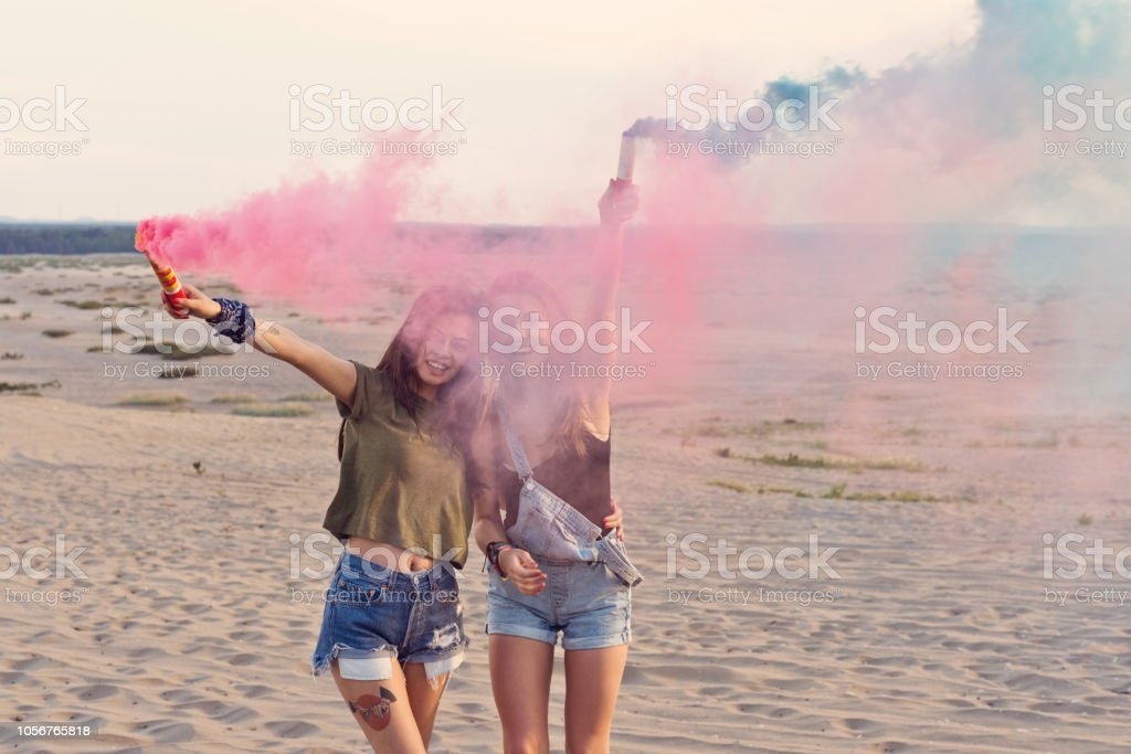 Happy friends playing with distress flare on the dune Two young women having fun on the desert, holding distress flare in hand. Adolescence Stock Photo