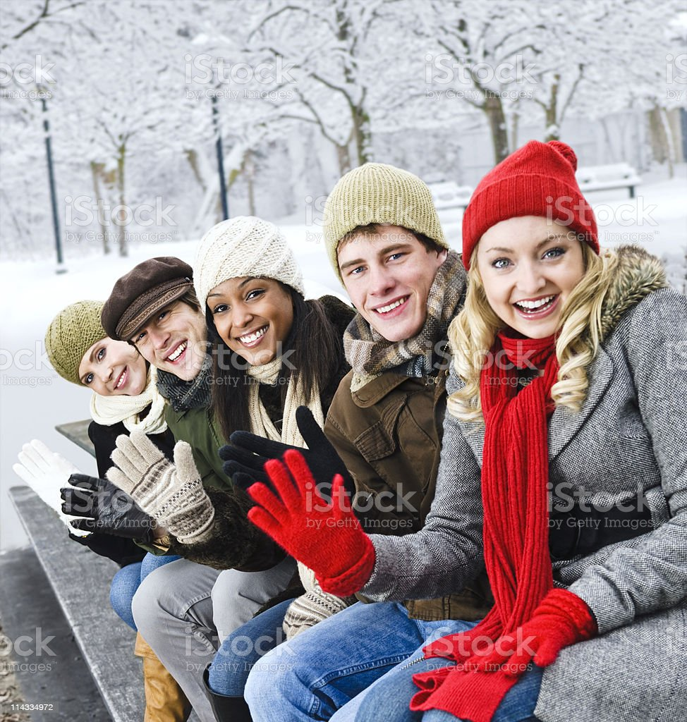 Happy friends posing on a bench in wintertime royalty-free stock photo
