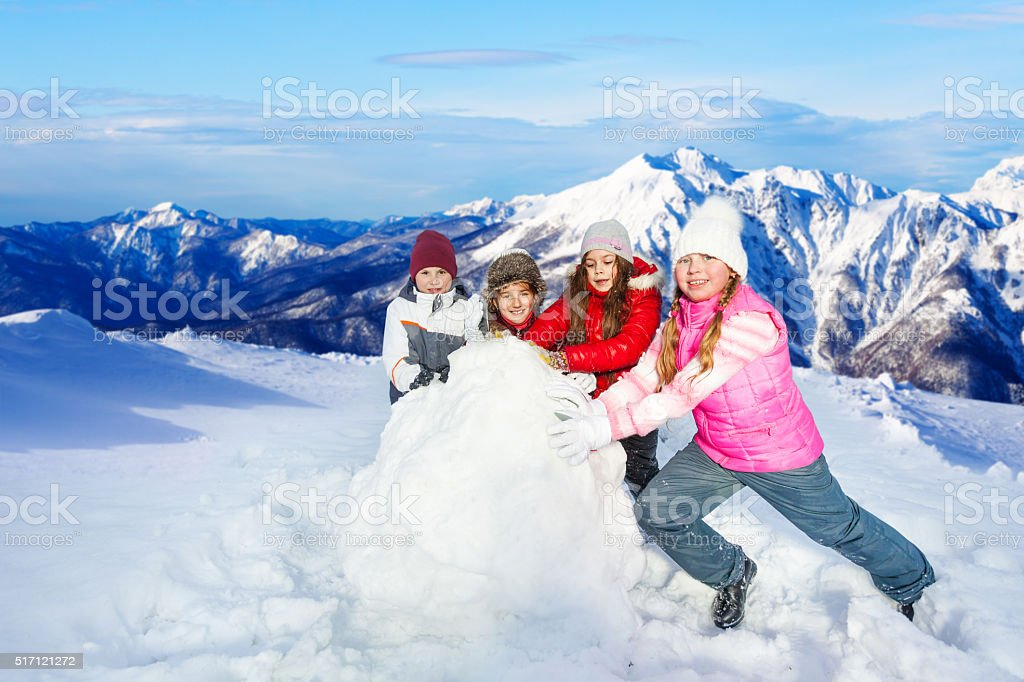 Happy friends rolling big snowball stock photo