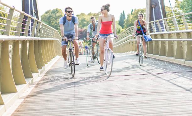 glückliche freunde, die fahrräder auf brücke stadtpark - junge leute, die spaß nach dem studium wieder zu hause - jugend, freundschaft und gesunden lifestyle-konzept - main fokus auf linke mädchen - radwege deutschland stock-fotos und bilder