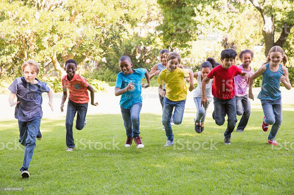 Happy friends running in the park stock photo