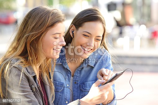 istock Happy friends sharing music on line 657407712