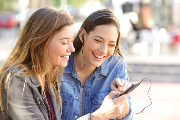 Happy friends sharing music on line stock photo