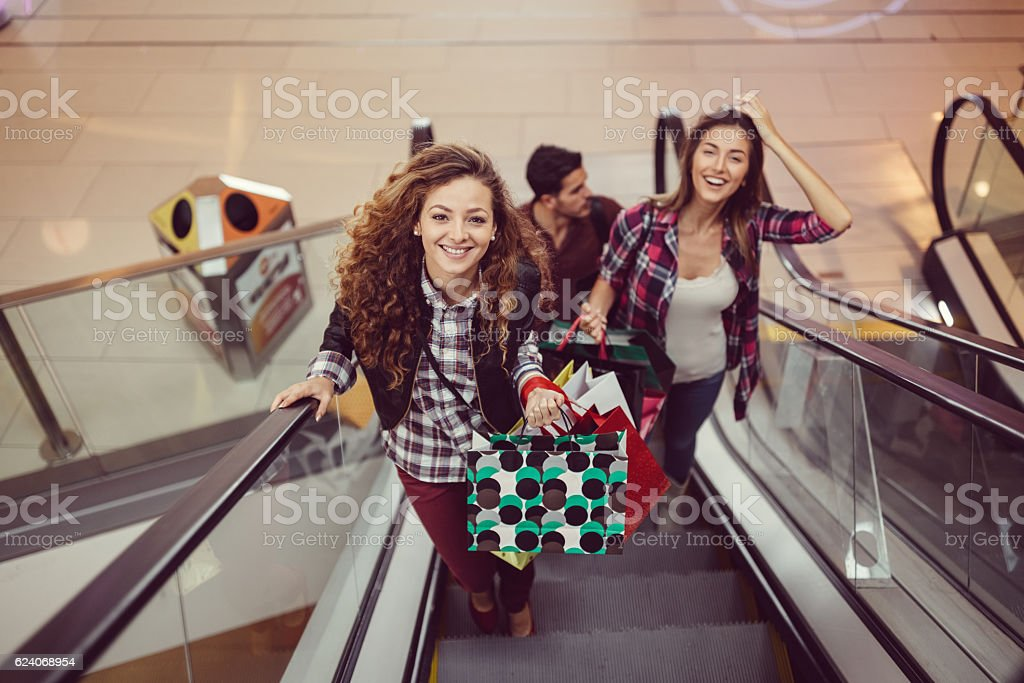 Happy friends shopping in the mall stock photo