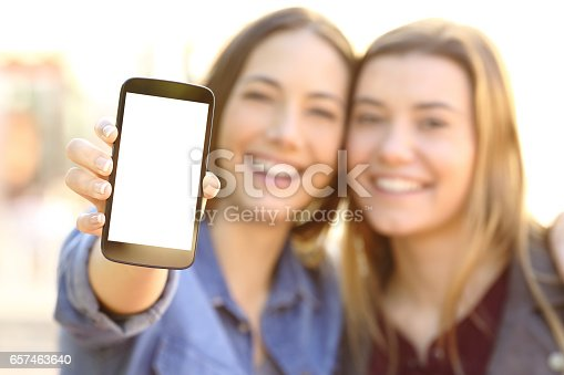 istock Happy friends showing a blank phone screen 657463640