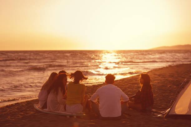 Glückliche Freunde, die während des Sonnenuntergangs am Strand sitzen und Gitarre spielen – Foto