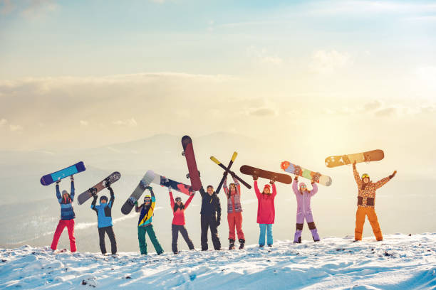 Happy friends skiers and snowboarders at ski resort