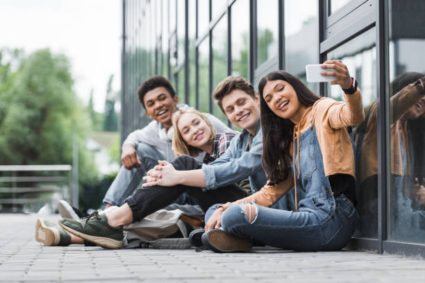 happy friends smiling, sitting and taking selfie with smartphone happy friends smiling, sitting and taking selfie with smartphone teenagers only stock pictures, royalty-free photos & images
