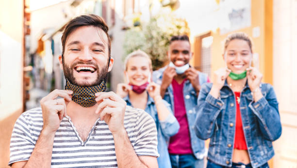 Happy friends smiling with opened face masks after lockdown reopening - New normal friendship concept with guys and girls having fun together on summer reunion - Bright filter with focus on left man stock photo