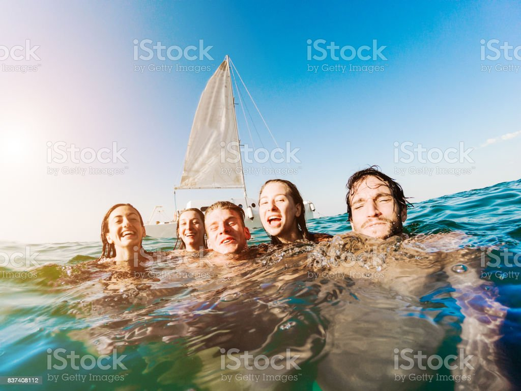 Happy friends swimming into the ocean next sailing catamaran boat - Young people having fun diving inside sea - Travel, tropical, youth, friendship and summer concept - Main focus on right guys stock photo