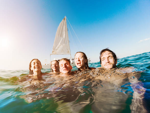 Happy friends swimming into the ocean next sailing catamaran boat - Young people having fun diving inside sea - Travel, tropical, youth, friendship and summer concept - Main focus on right guys - fotografia de stock