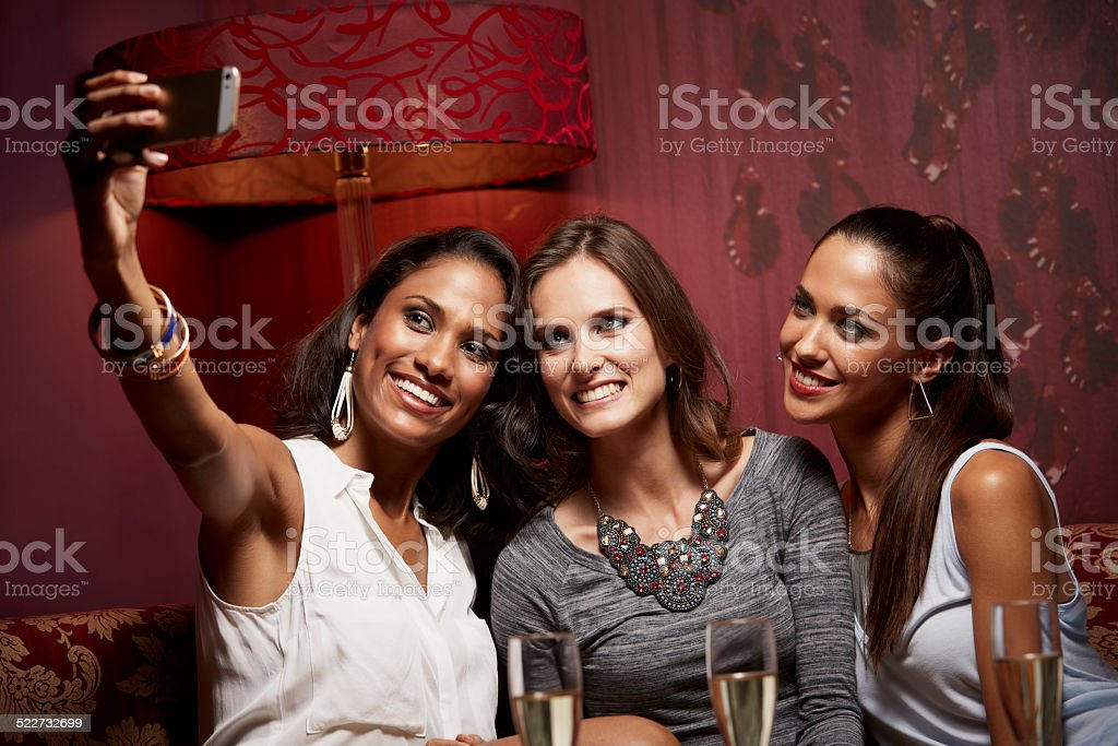 Happy friends taking self portrait at nightclub stock photo