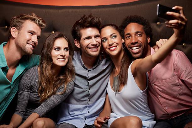 happy friends taking self portrait at nightclub - club sofa stock-fotos und bilder